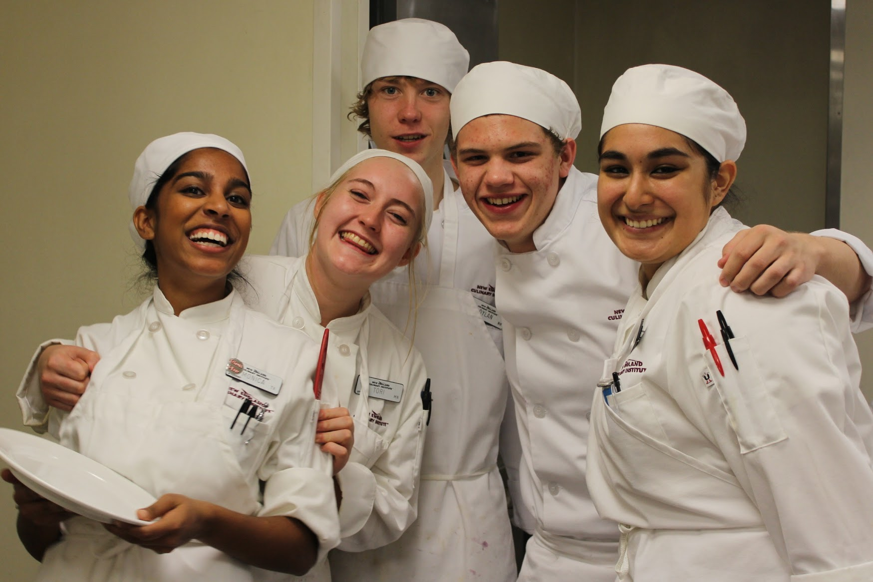 Five smiling students chefs pose for the camera